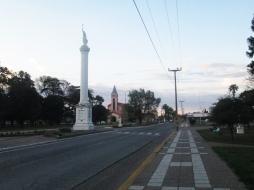 """La ruta 12 pasa por el centro del pueblo. En medio de las dos cuadras de la plaza está la """"Pirámide"""". Atrás se ve la iglesia."""