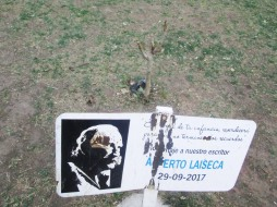 Homenaje a Alberto Laiseca, en la plaza del pueblo. Plantaron el pequeño nogal que se ve atrás y colocaron el letrero, que ahora está vandalizado. (En ese mismo lugar, los chicos del pueblo juegan a la pelota; ya jugaban a la pelota antes del cartel, así que se puede decir que tenían prioridad.)